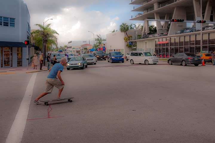skateboarder nervously looks to cross traffic-clogged Alton Road in Miami Beach