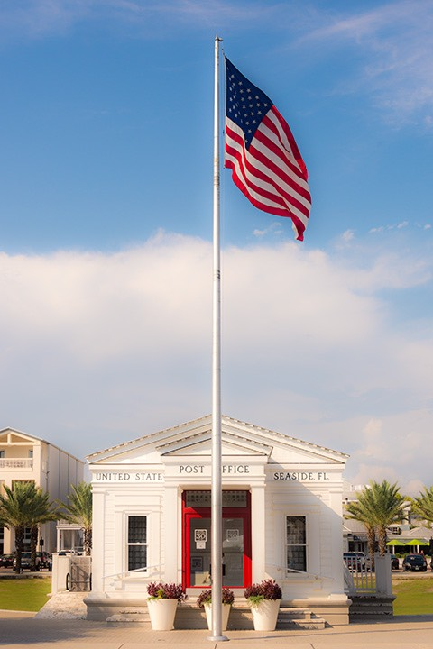 American flag waving in the sea breeze of Seaside, Florida just in front of white clapboard post office