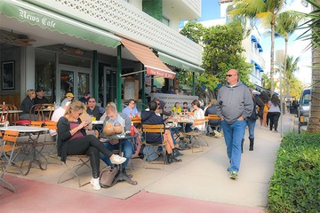 tourists stroll along Ocean Drive on South Beach as patrons enjoy brunch at the News Cafe