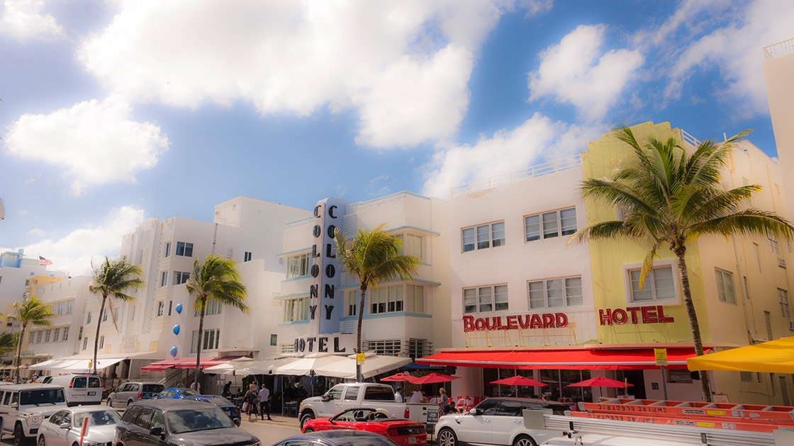 palm trees march by the iconic Art Deco hotels on South Beach's Ocean Drive