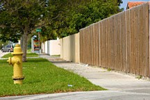 stockade-fenced back yards backing up to arterial thoroughfare in Miami, Florida
