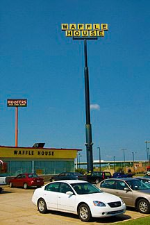Waffle House with enormous pylon sign and interstate bridge in the background