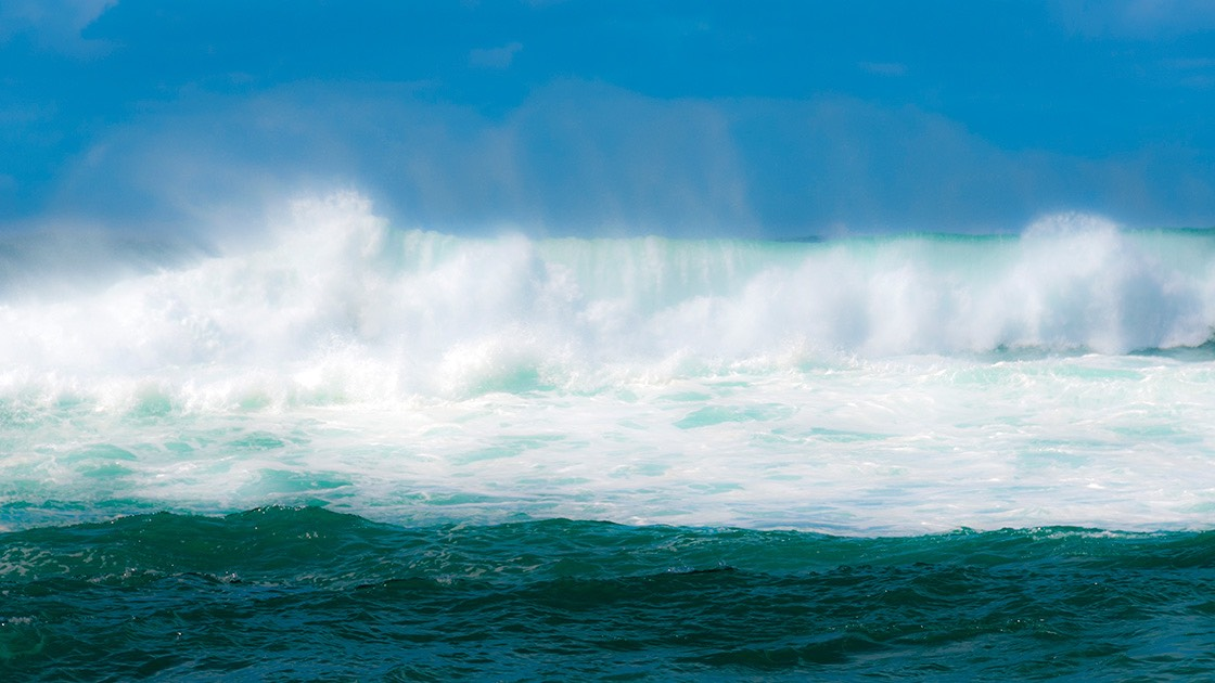 foaming waves and their salt spray crashing against a deep blue Hawaiian sky