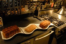 bread and cinnamon rolls in three with plates sitting on black soapstone countertop