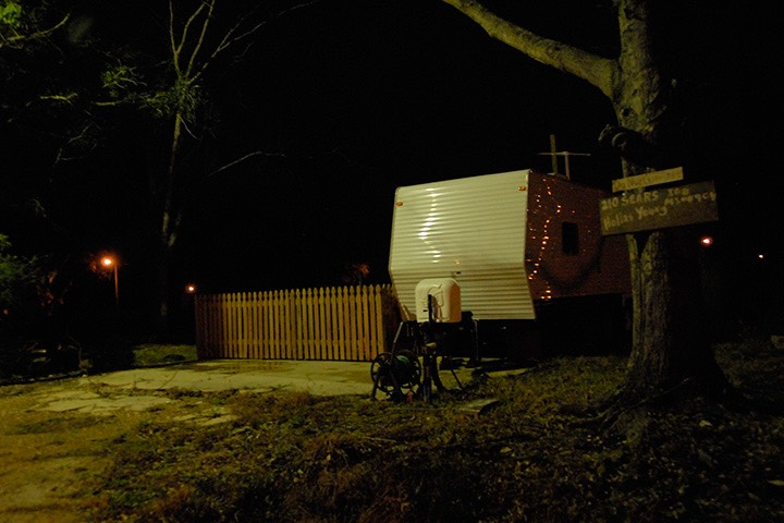 FEMA trailer glows a dim green against the post-Katrina darkness, as a picket fence stakes out territory against the night