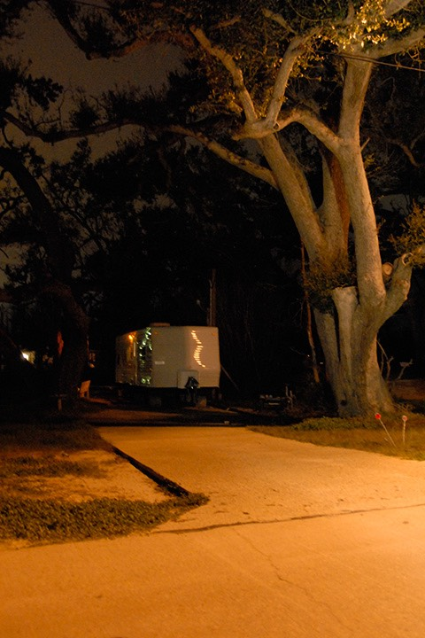 FEMA trailer sits at the dark end of a driveway underneath a Katrina-brutalized oak tree in Gulfport, Mississippi, reflecting distant street lights