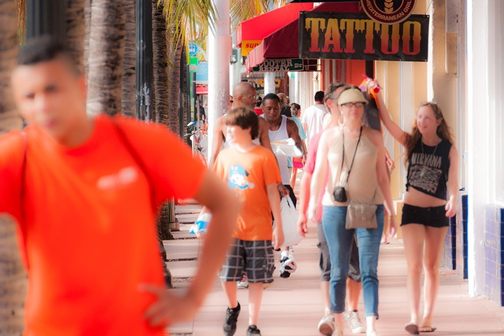 brightly-clad vacationers strolling past one of Washington Avenue's several tattoo parlors on South Beach