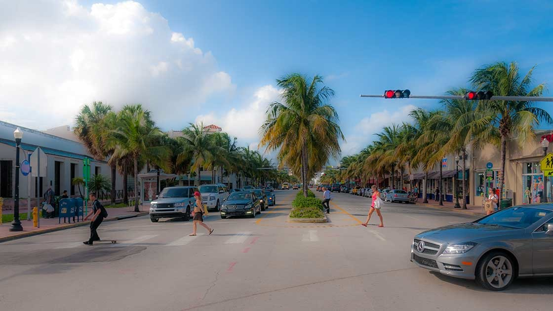 walkers and a skateboarder safely crossing sun-drenched and palm-lined stretch of Washington Avenue on South Beach