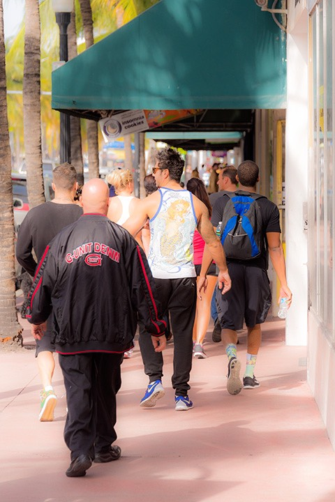 a pack of sturdy young men amble along the South Beach sidewalks of Washington Avenue, one with a black windbreaker and another in a white tank top - is it a warm day or not?