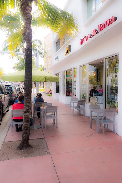 Washington Avenue sidewalk cafe on South Beach protected by a wall of parked cars