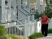 two women visiting at the Waters near Montgomery, Alabama; one leaning on her porch rail and the other leaning against the front picket fence